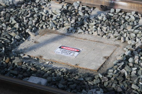 'Danger confined space' signage on a drainage pit between the tracks