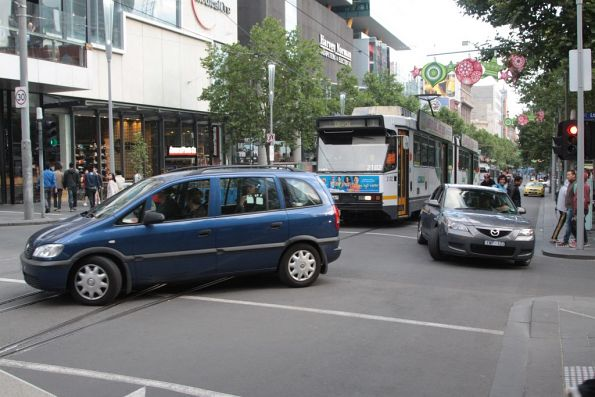 Confused motorists finally clear the intersection, after a tram driver gave them directions