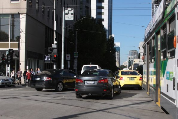 Dimwitted motorists queue through the intersection of La Trobe and William Streets, delaying an eastbound tram