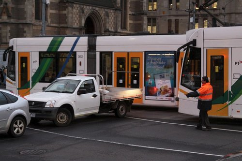 Yarra Trams operational staff ask motorists to clear the tracks at the corner of Swanston and Flinders Streets