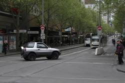 After realising they can't drive through the tram stop, this motorist makes a last minute U-turn at Bourke Street