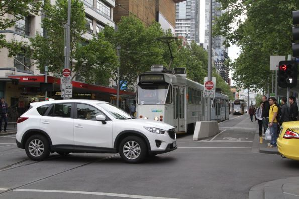 Another car delaying trams at the corner of Swanston and Little Lonsdale Streets