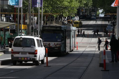 Campervan pulls up behind a stationary tram at the Elizabeth Street stop