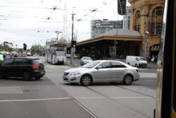 Silver car blocks trams in both directions at Swanston and Flinders Streets