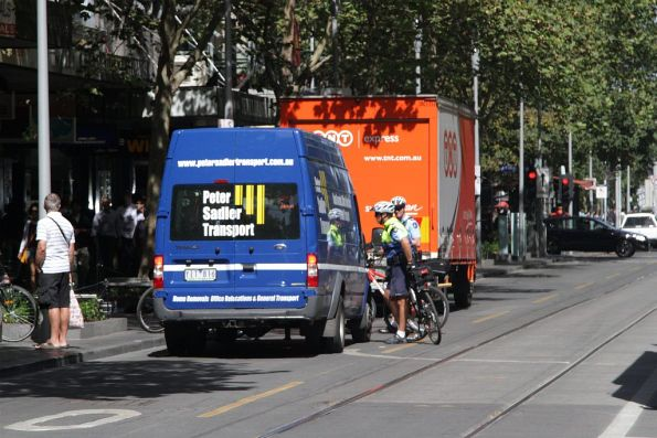 Victoria Police officers on bike patrol talk to the van that drove through a Swanston Street tram stop