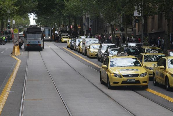 Another taxi driver on Collins Street undeterred by the new plastic kerbs along the tracks