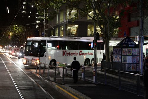 Road coach reverses back out of Elizabeth Street, having been unable to make the turn from La Trobe Street due to the tram stop