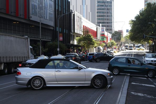 Four cars all attempt a u-turn across raised tram tracks on Spencer Street
