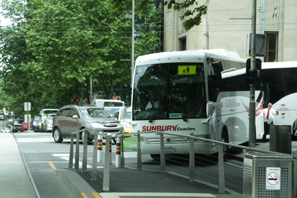 Driver of a road coach gets some assistance from a following bus, as he tries to make it past the tram stop from William Street into Collins Street