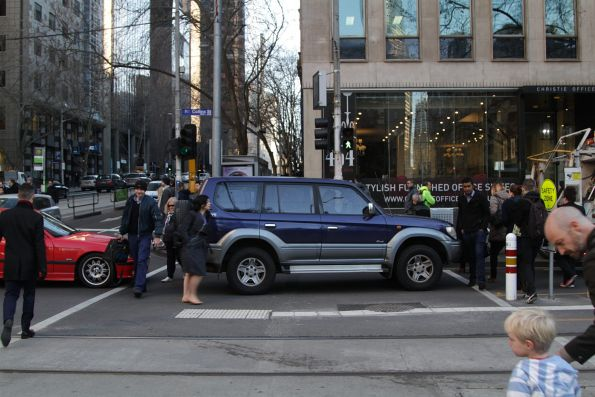 Motorist queues through the pedestrian crossing at Collins and William Street