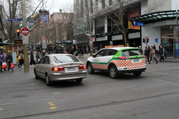 Yarra Trams staff direct a confused motorist away from the corner of Swanston and Bourke Street