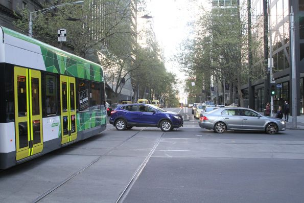 Queued cars delay trams at the corner of Bourke and William Street