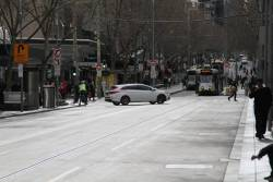 Confused motorist correctly chooses to u-turn at the corner of Swanston and Bourke Street