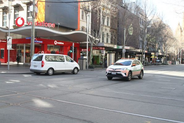 Confused motorist does a u-turn at the Swanston and Bourke Street tram stop