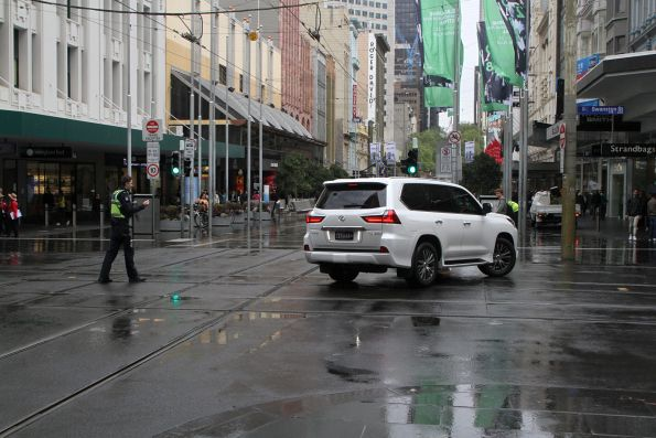 Victoria Police officer guides the confused motorist out of the corner of Swanston and Bourke Street