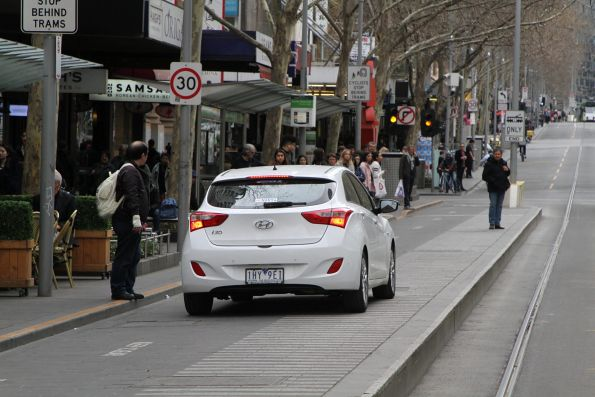 Pedestrian has a go at a senile old man driving through the tram stop at Swanston and Bourke Street