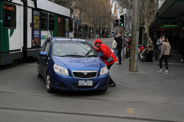 City of Melbourne tourist volunteer redirects a confused motorists at the corner of Swanston and Bourke Street