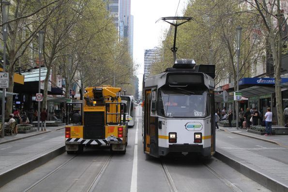 Driver of a Franna crane heads through the tram stop at Swanston and Bourke Street