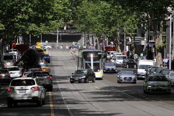 Tram E.6023 on route 96 along Bourke Street delayed by a car turning right into a side street