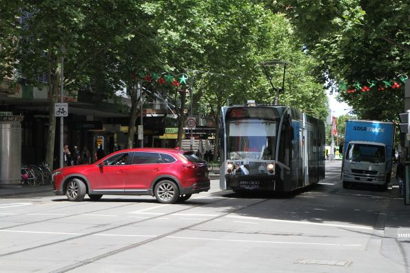 Car doing a u-turn at Swanston and Bourke Street blocks tram D1.3506 advertising 'Jimmy Choo' on route 5