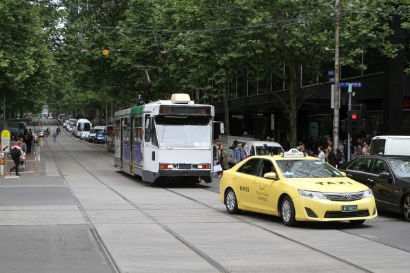 A1.240 headed east on route 12 waits for a taxi blocking the tram tracks at Collins and Elizabeth Street