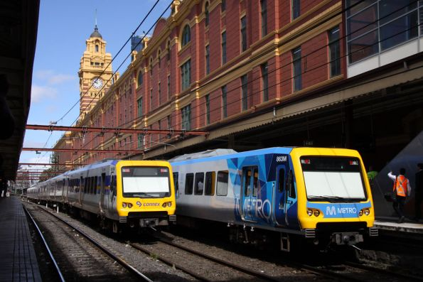 Connex and Metro liveried X'Trapolis trains pass at Flinders Street Station