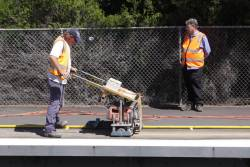 Metro staff watch for approaching trains, as work continues on drilling the holes