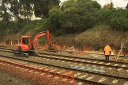 Excavator at work on new retaining walls beside the Caulfield Through tracks