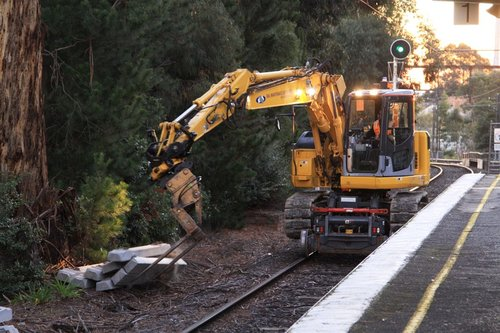 Hi-rail excavator dropping off sleepers beside the tracks at Jordanville