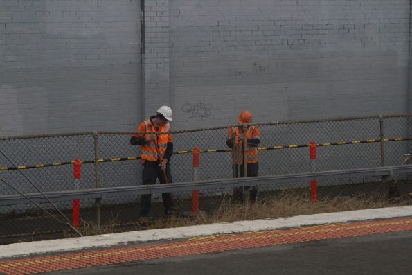 Workers replacing the old chain-link fence at Burnley with a new metal picket fence