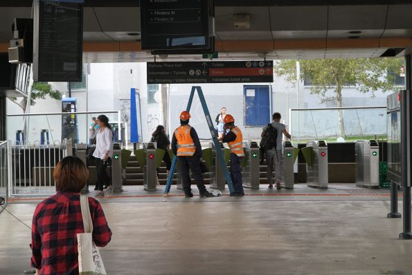 Metro staff replace a CCTV camera at North Melbourne Station