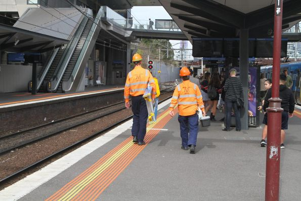 Metro staff at work repairing next train displays at North Melbourne station