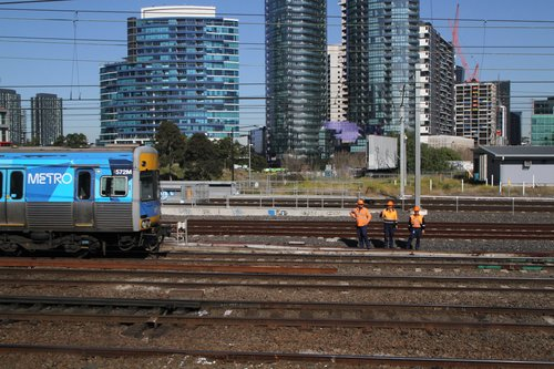Alstom Comeng train 572M passes metro staff inspecting the tracks at Franklin Street