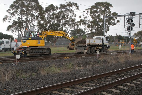 Hi rail excavator and dump truck at work clearing a mud hole on the Sunbury line at Albion