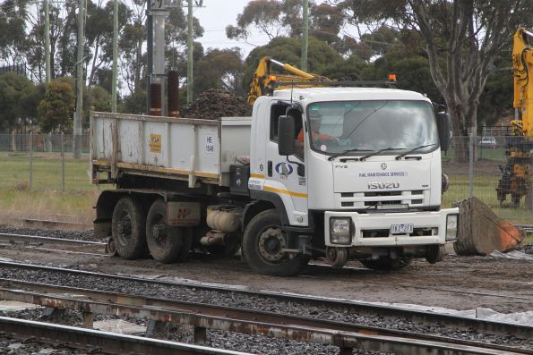 Dump truck raises the hi rail wheels to exiting the work site  on the Sunbury line at Albion