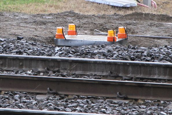 Warning lights sitting atop a concrete drainage pit brside a hi rail access pad