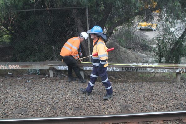 Flagman keeps watch at North Melbourne Junction while someone else works on the signal trunking