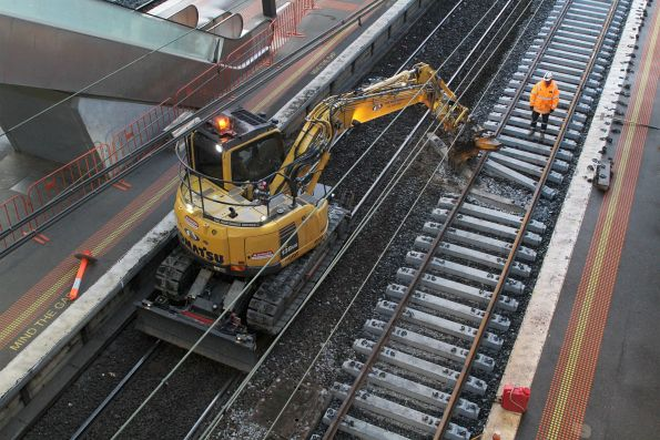 Excavator at work moving concrete sleepers into position at North Melbourne platform 1