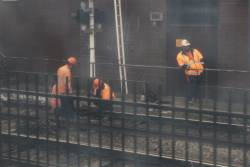 Metro Trains staff attend to the points at the up end of North Melbourne station during morning peak