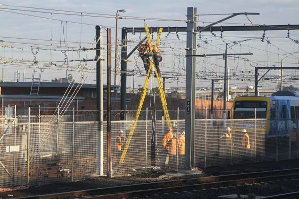 Metro crew atop ladders to repair the overhead wire at Melbourne Yard