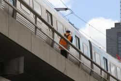 Metro Trains staff wait for a train to pass on the Flinders Street Viaduct