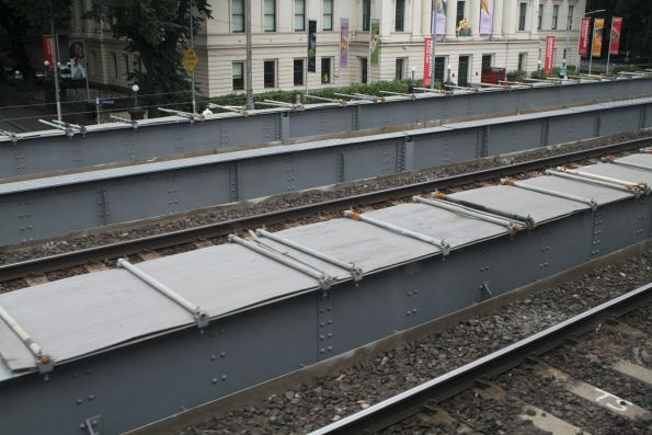 Scaffolding and plywood covers the partially sandblasted and repainted Flinders Street Viaduct