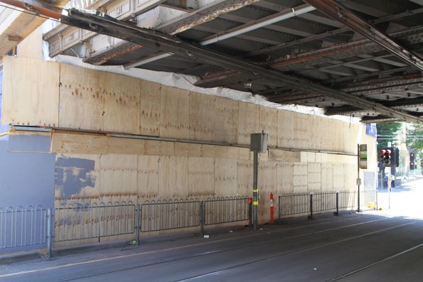 Plywood hoarding covers the section of the Flinders Street Viaduct currently being repainted