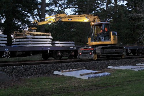 Hi-rail excavator unloading another 8 concrete sleepers
