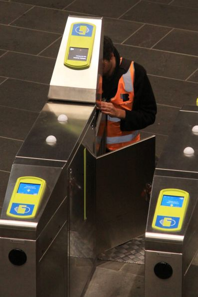 Bytecraft technician fiddling with the Myki-only barriers for the Southern Cross country platforms