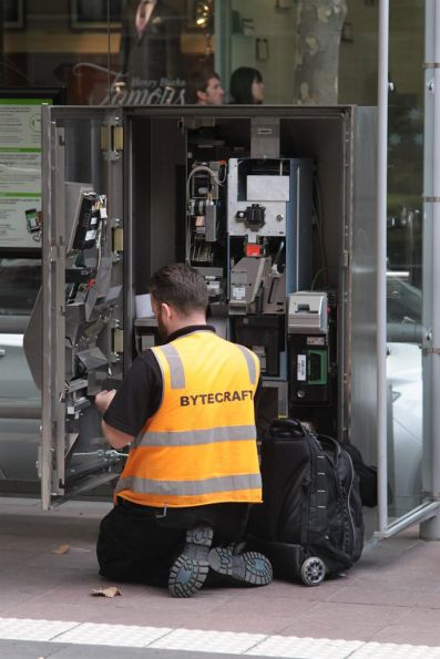 Technician working on the innards of a Myki ticket machine