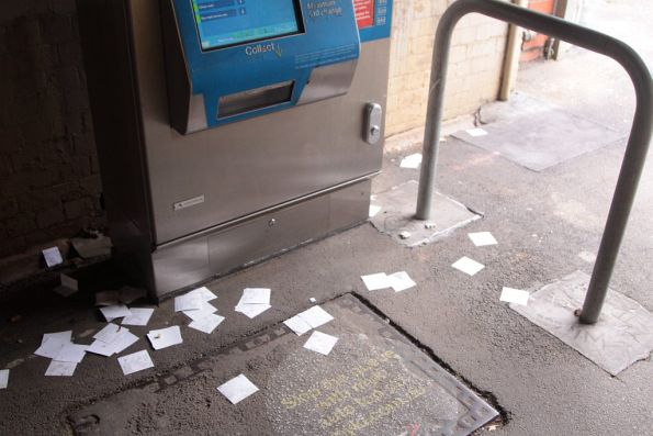Unwanted Myki receipts litter the ground below the ticket machine at South Kensington