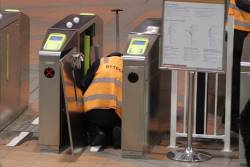 Bytecraft technician works to fix a defective Myki gate at Flagstaff station