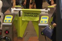 'Temporarily Unavailable' flags blocking access to a broken Myki reader at Flagstaff station