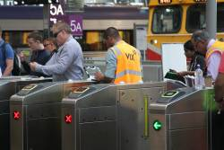 Vix technician fixing a defective set of myki gates at Southern Cross Station